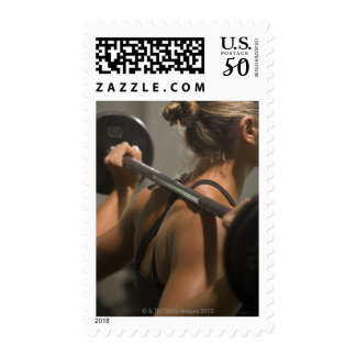 Young woman exercising with barbell, rear view postage