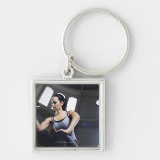 Young woman exercising with dumbbell key chains