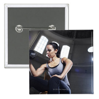 Young woman exercising with dumbbell pinback button