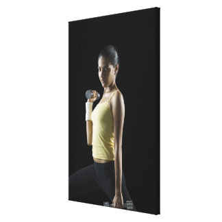 Young woman exercising with dumbbells gallery wrapped canvas