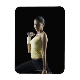 Young woman exercising with dumbbells magnet