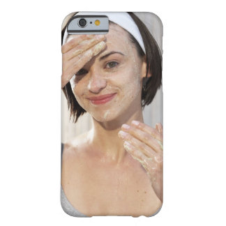 Young woman exfoliating face, smiling, portrait, barely there iPhone 6 case