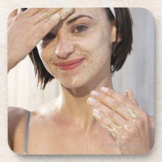 Young woman exfoliating face, smiling, portrait, coaster