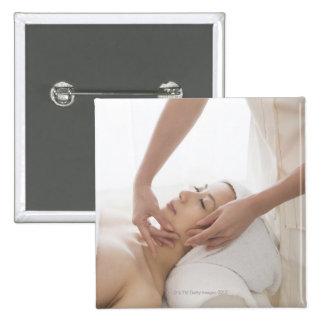 Young woman having facial massage button