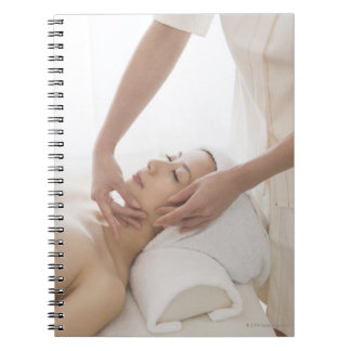 Young woman having facial massage notebook