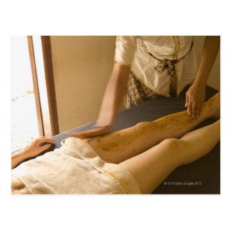 Young woman having leg massage post card
