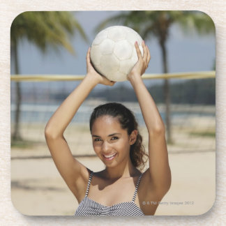 Young woman holding volleyball and smiling at coaster