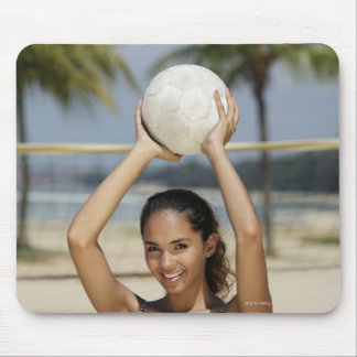 Young woman holding volleyball and smiling at mouse pad