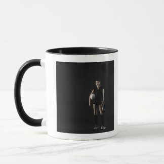 Young woman holding volleyball, portrait mug