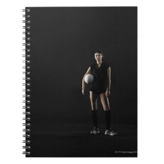 Young woman holding volleyball, portrait notebook