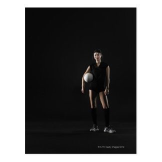 Young woman holding volleyball, portrait post card