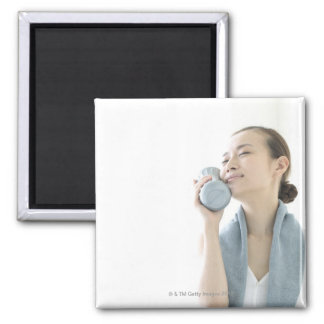 young woman holding water bottle to face 2 inch square magnet