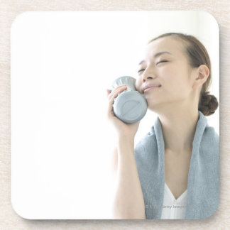 young woman holding water bottle to face drink coaster