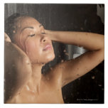 Young woman in shower ceramic tiles