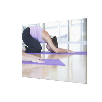 young woman in the downward dog position during canvas print