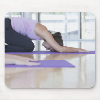 young woman in the downward dog position during mouse pad