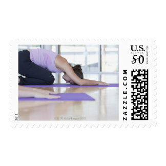 young woman in the downward dog position during postage