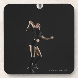 Young woman jumping to hit volleyball, side view beverage coaster