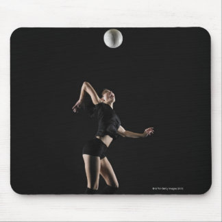 Young woman jumping to hit volleyball, side view mouse pad