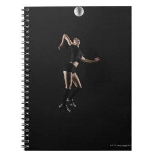 Young woman jumping to hit volleyball, side view notebook