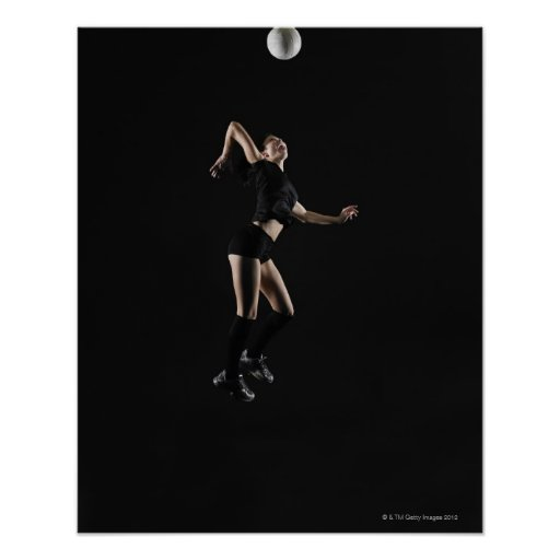Young woman jumping to hit volleyball, side view poster