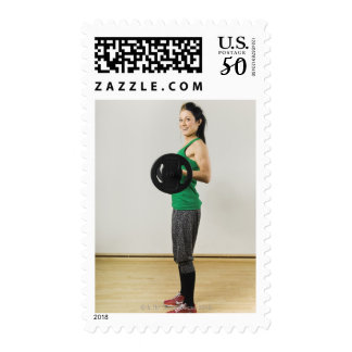 Young woman lifting a barbell. postage