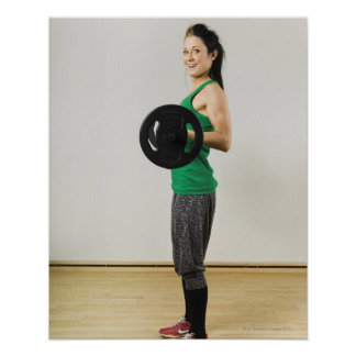 Young woman lifting a barbell. posters