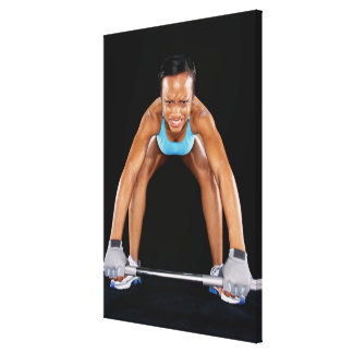 Young woman lifting barbell, portrait canvas print