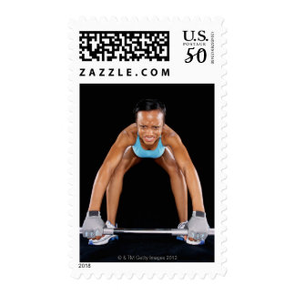 Young woman lifting barbell, portrait postage