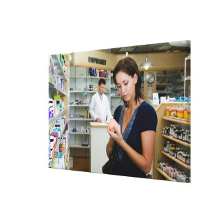 Young woman looking at medicine in pharmacy, canvas print
