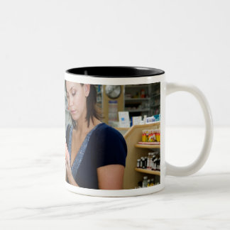 Young woman looking at medicine in pharmacy, coffee mug
