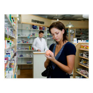 Young woman looking at medicine in pharmacy, postcard