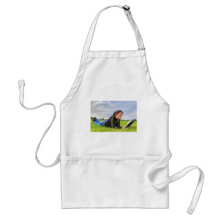 Young woman lying in grass reading book adult apron