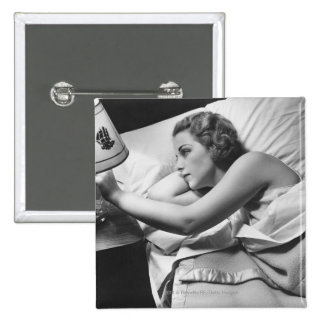 Young woman lying on bed turning off lamp on pin