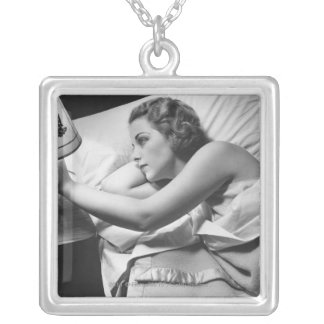 Young woman lying on bed turning off lamp on silver plated necklace