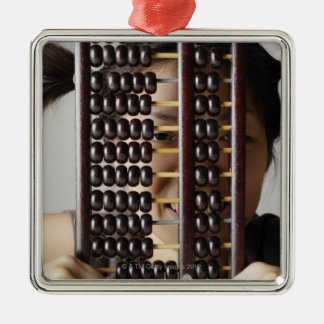 Young woman peering through abacus. ornaments