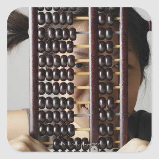 Young woman peering through abacus. square sticker