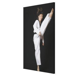 Young woman performing front kick canvas print