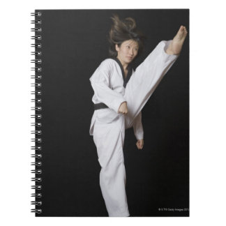 Young woman performing front kick notebook
