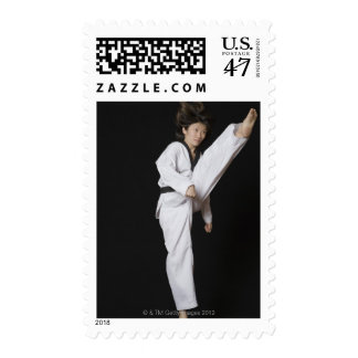 Young woman performing front kick postage