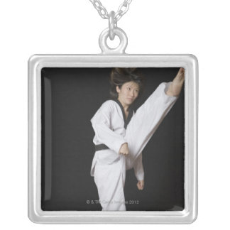 Young woman performing front kick silver plated necklace