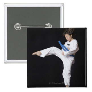 Young woman performing round kick 2 inch square button