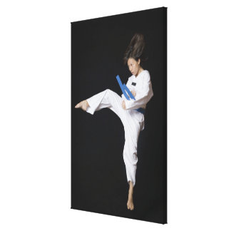 Young woman performing round kick canvas print