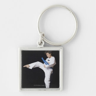 Young woman performing round kick key chains