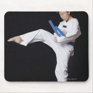 Young woman performing round kick mouse pad