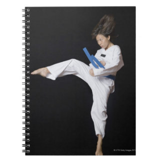 Young woman performing round kick spiral notebooks