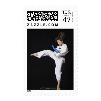 Young woman performing round kick postage