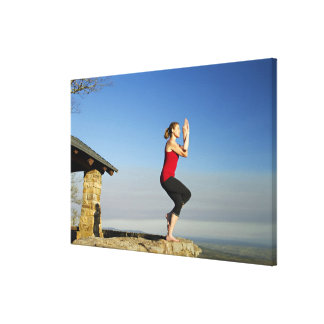 young woman practices yoga on a bluff in the canvas print