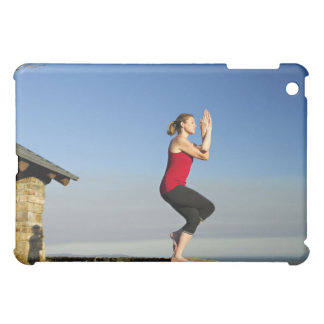 young woman practices yoga on a bluff in the case for the iPad mini