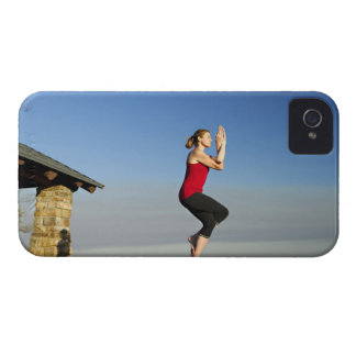 young woman practices yoga on a bluff in the iPhone 4 case